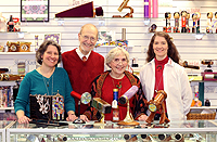 Jan and Bobby at Christmastime, in the shop behind the counter with their two daughters, Emily with short hair in blue, and Ginger with long hair and a white sweater