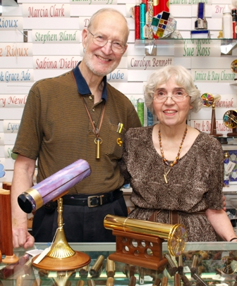 Jan and Bobby standing in the corner of a store surrounded by kaleidoscopes and gifts. He is tall and she is shorter, they both have glasses, white hair, and warm, genuine smiles.